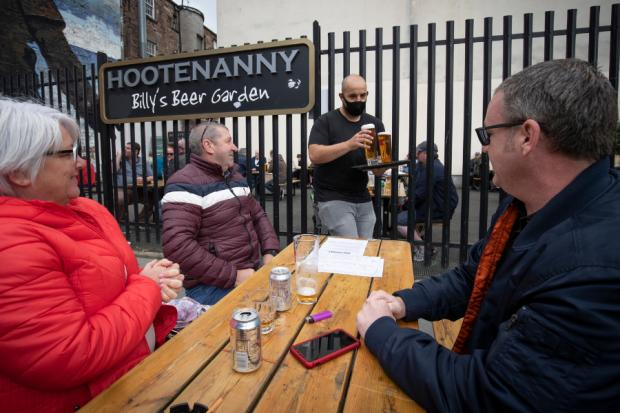 Helensburgh Advertiser: Members of the public enjoy their first drink in a beer garden at the Hootenanny, Glasgow.