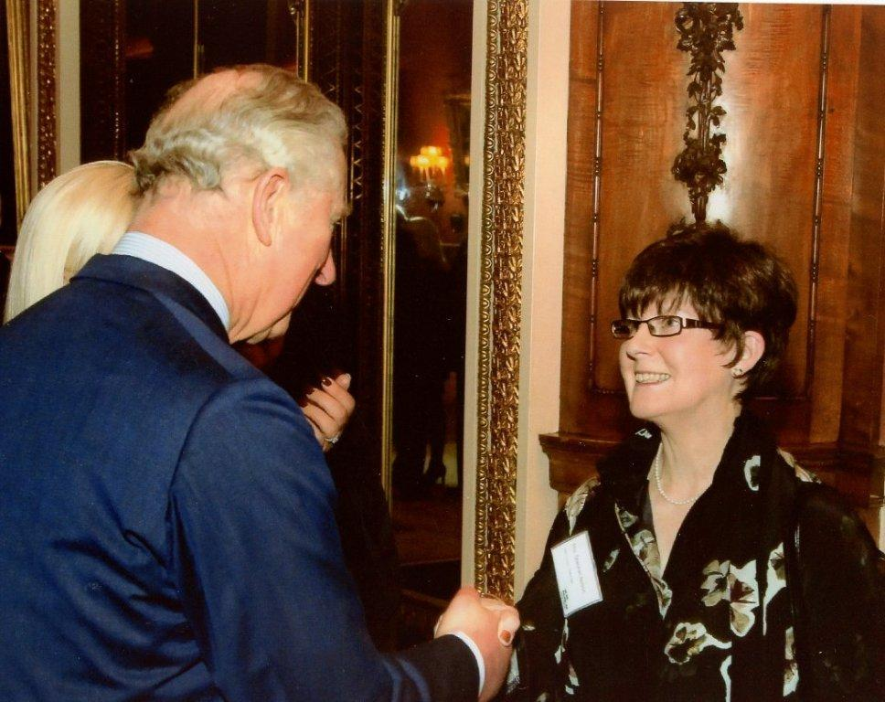 Prince Charles welcomes Sheenah Nelson to a reception in Buckingham Palace for Macmillan Cancer Care supporters