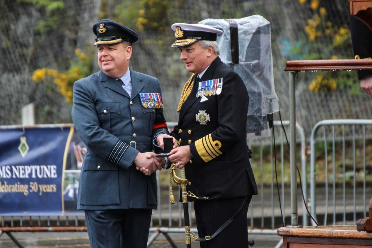 Admiral Sir Philip Jones presents a long service medal to Group Captain Kevin Bailey, deputy head of naval base security
