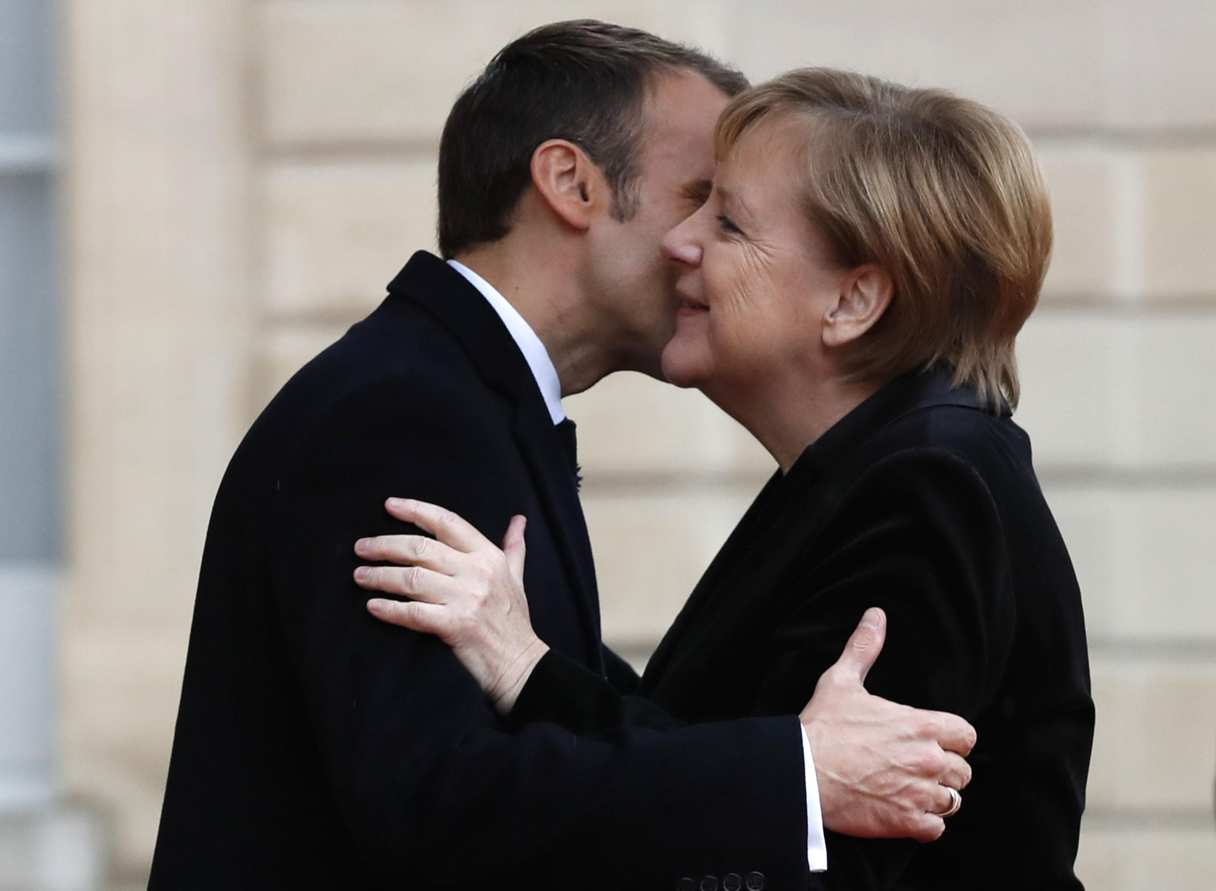 French President Emmanuel Macron hugs German Chancellor Angela Merkel in the courtyard of the Elysee Palace Sunday, Nov. 11, 2018 in Paris. International leaders are taking place in a ceremony in Paris on Sunday at mark the 100th anniversary of the end of