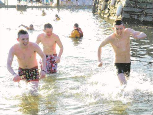 Some of the hardy swimmers who took the plunge in the freezing cold waters in Rhu on New Year's Day